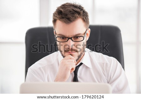 Full concentration at work. Handsome young beard man in shirt and tie working on laptop while sitting at his working place - stock photo