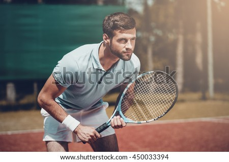 Full concentration. Handsome young man in polo shirt holding tennis racket and looking concentrated while standing on tennis court - stock photo