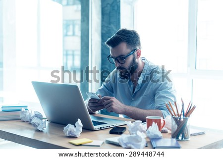 Full concentration on work. Concentrated young beard man looking at his mobile phone while sitting at his working place in office - stock photo