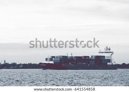Full container ship moving to Baltic sea. Riga, Latvia