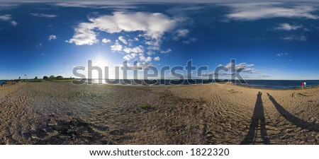 full 360 degree panorama of a beach on a peninsula on a sunny afternoon. Complete with puffy white clouds and blue sky. - stock photo