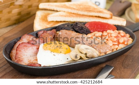 Full English Breakfast - Traditional English fry-up with egg, bacon, mushrooms, tomatoes, sausage, black pudding and baked beans. Served with slices of toast.