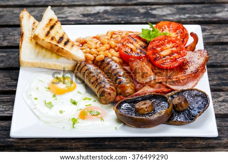 Full English breakfast with bacon, sausage, egg, beans and mushrooms - stock photo
