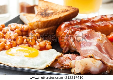 Full English breakfast with bacon, sausage, fried egg, baked beans and orange juice - stock photo