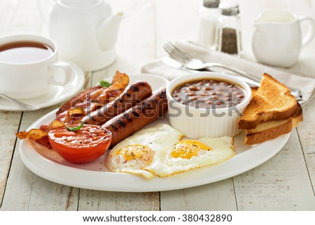Full english breakfast with egg, sausage and bacon - stock photo