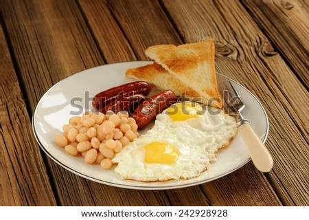 Full english breakfast with eggs, sausages, beans, toasts  - stock photo