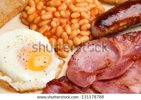 Full English cooked breakfast with bacon, sausage, fried egg and baked beans. - stock photo