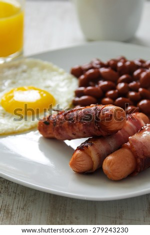 Full English cooked breakfast with bacon, sausage, fried egg and baked beans - stock photo