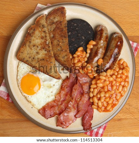 Full English fried breakfast with bacon, egg, sausages, black pudding and baked beans. - stock photo
