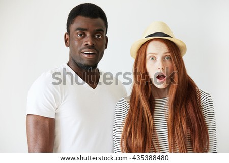 Full face portrait of surprised couple in white studio. Red head girl with long hair and summer hat stands still with opened mouth in astonishment, Afro man is also staring at camera with big eyes.