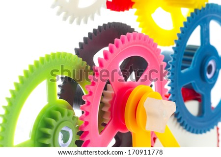 full-frame background multicolor clockwork cogs isolated on white with selective focus - stock photo