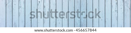 Full frame, large and wide shot of an old, weathered, light pastel blue wooden wall.