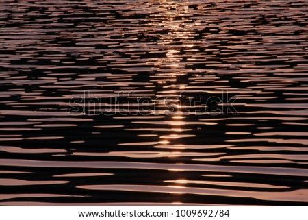 Full frame light of sunset reflected in the water