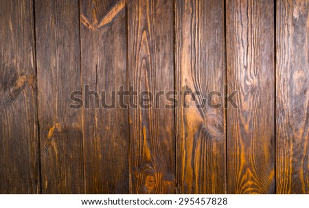 Full frame of dark brown wooden floorboards shot from directly above, with knots in wood and gaps between boards - stock photo