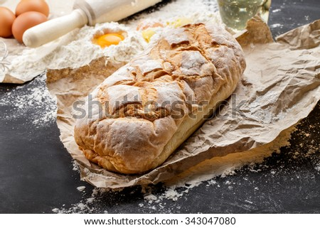 full frame of homemade rustic bread on black board - stock photo