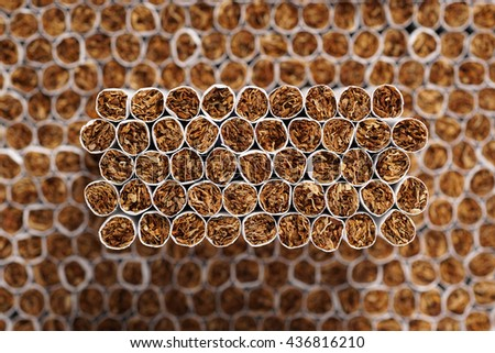 Full frame of stacked cigarettes as background or texture. Selective focus on the tip of one cigarettes