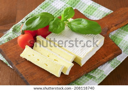 full frame of wooden cutting board with surface ripened cheese and fresh tomatoes