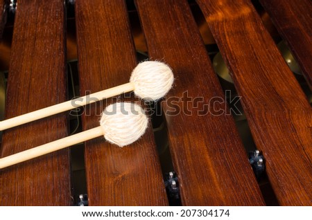 Full frame take of two mallets resting on the keys of  a marimba - stock photo