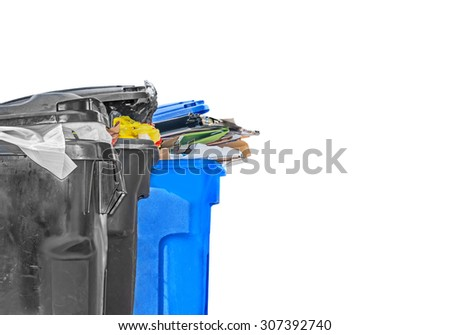 Full garbage and recycling bins. Plastic black and blue waste cans filled with rubbish isolated on a white background. Copyspace.   - stock photo