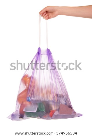 Full garbage bag with drawstring keeps the hand isolated on white background - stock photo