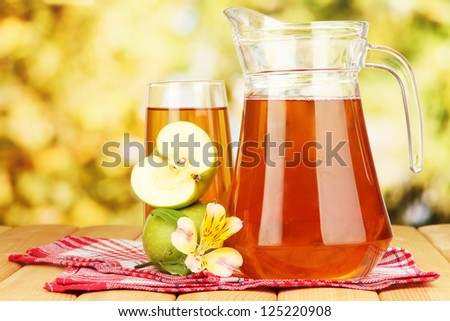 Full glass and jug of apple juice and apples on wooden table outdoor - stock photo