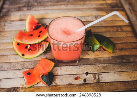 Full glass of a creamy and bubbly watermelon shake smoothie with a slice of watermelon and glass tube. Sliced watermelon and paper decorative on brown wood board  background in rustic style. - stock photo