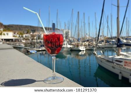 Full glass of sangria against marina of Puerto de Mogan. Gran Canaria, Spain - stock photo