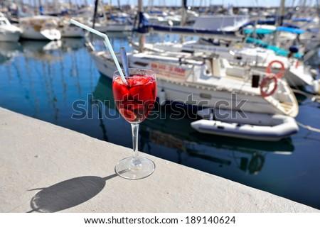 Full glass of  strawberry sungria against marina of Puerto de Mogan. Gran Canaria, Spain - stock photo