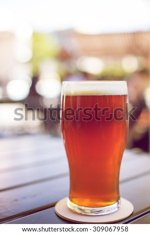 Full glass of tasty craft beer on a coaster on table in a outdoor pub - stock photo