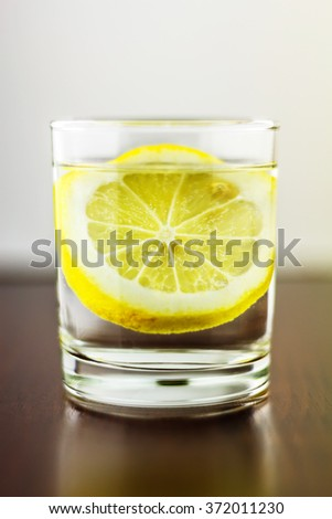Full glass of transparent purified water with slice of lemon, on wooden table, and blurred white background - stock photo