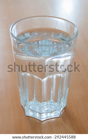 Full glass of water glass on a wooden table - stock photo