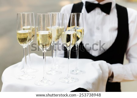 Full glasses of champagne on tray - stock photo