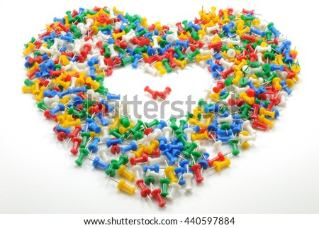 Full heart shape of colorful push pins with empty space and two red pins inside, isolated on white background.