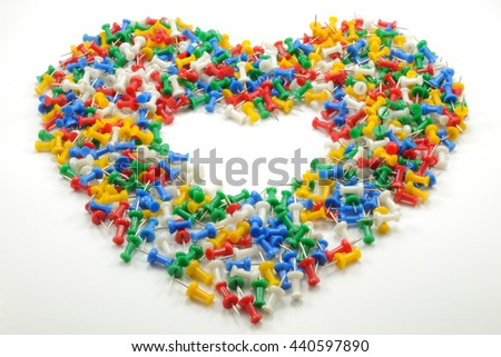 Full heart shape of colorful push pins with empty space inside, isolated on white background.