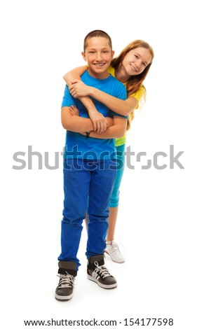 Full height portrait of couple of kids hugging together and standing isolated on white - stock photo