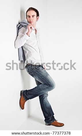 Full height portrait of young man leaning to a white wall - stock photo