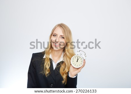 Full isolated portrait of a beautiful caucasian businesswoman locking at the clock with pointer 5 to 12.