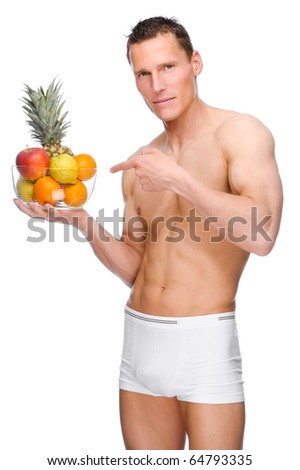 Full isolated studio picture from a young naked man with some fruit