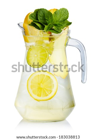 Full jug of fresh birch juice with lemon, ginger and mint leaves isolated