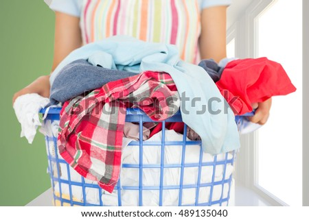 Full laundry basket against modern white and green room with window