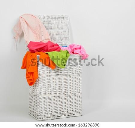 Full laundry basket isolated on white - stock photo