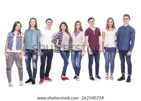 Full lenght. Happy  smiling young group standing and looking at camera. isolated on white background. - stock photo