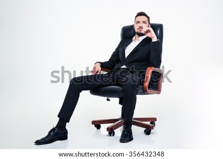Full lenght of assured confident young business man with beard in black suit sitting in office chair and looking camera over white background - stock photo