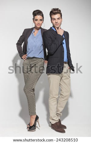 Full lenght picture of a young fashion couple posing on light grey background, both looking at the camera. - stock photo