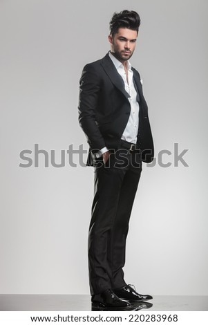 Full lenght picture of an elegant young man in tuxedo, looking away from the camera while holding his hands in pocket. On grey background. - stock photo