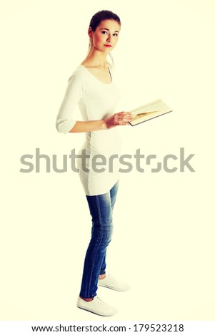 Full lenght portrait of a beautiful young caucasian teen holding a book - stock photo