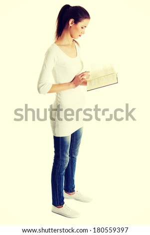 Full lenght portrait of a beautiful young caucasian teen reading a Bible, on white.