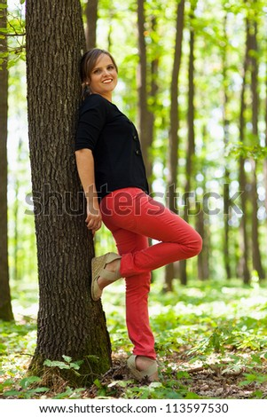 Full lenght portrait of a young beautiful woman leaning on a tree in the woods - stock photo