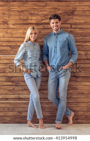 Full lenght portrait of beautiful young couple in jeans clothes looking at camera and smiling, standing hands in pockets against wooden wall - stock photo