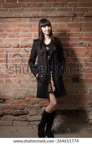 Full lenght young women smiling against red brick wall - stock photo